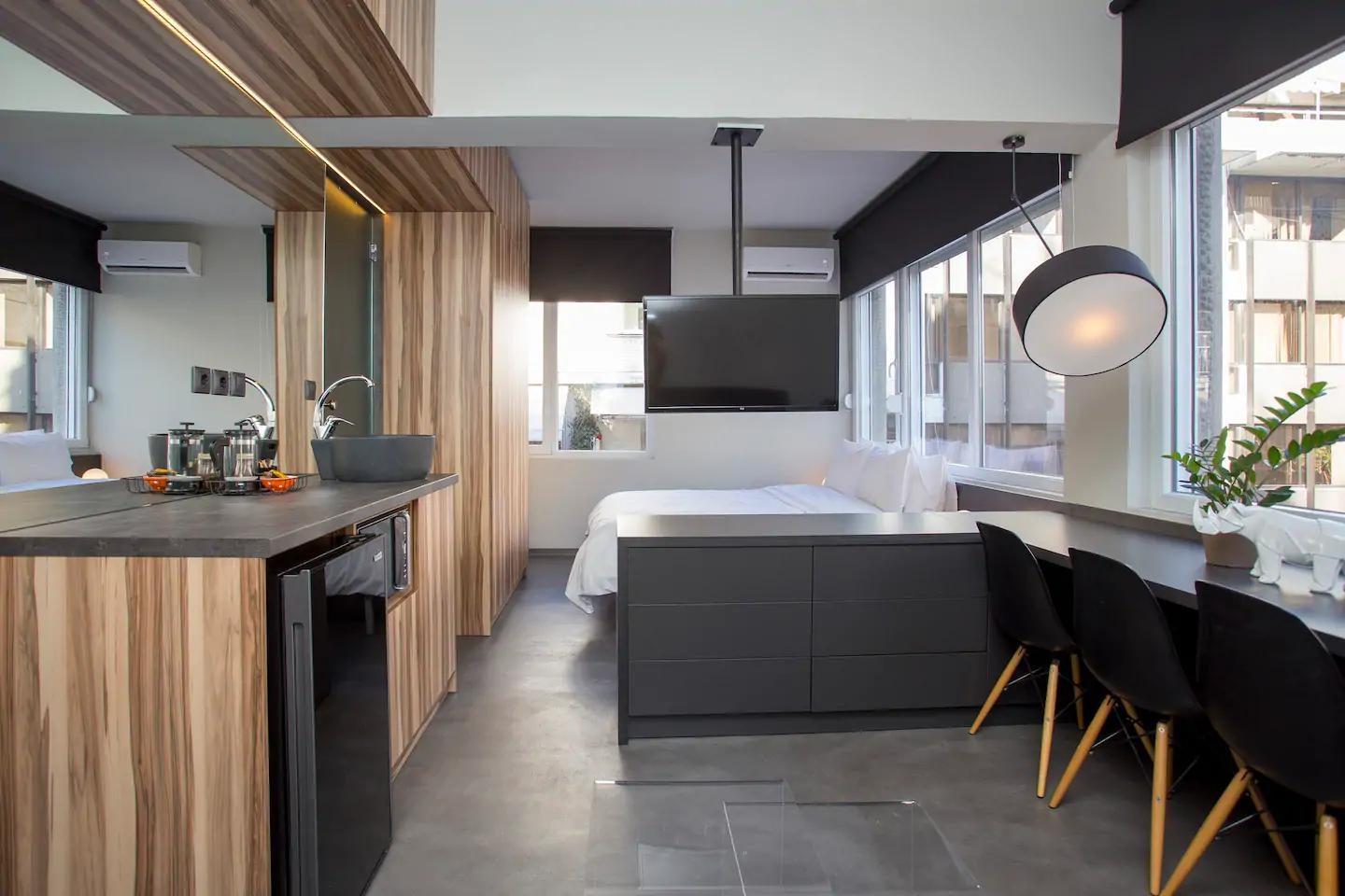 Modern black and wood studio with white bed